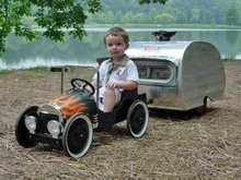 Kid with pedal car and trailer. Is that a mini Airstream?